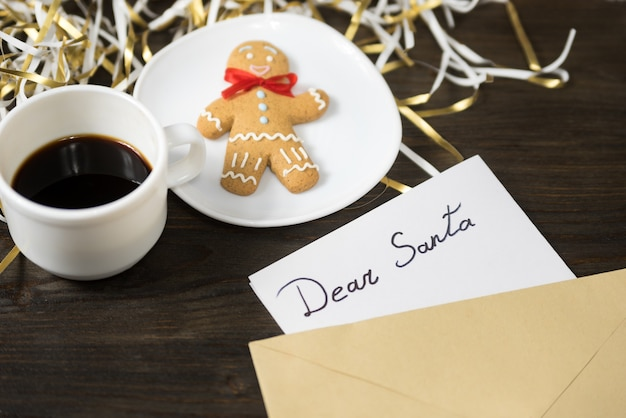 Letter for santa in an envelope. gingerbread and coffee on background