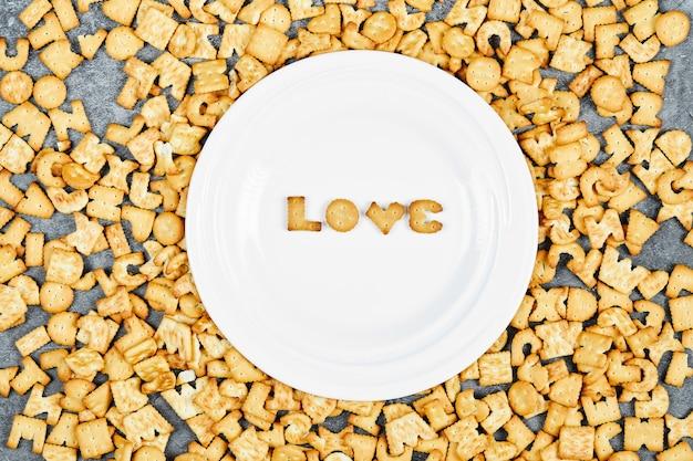 Крекеры в форме буквы на земле и в белом блюдце.