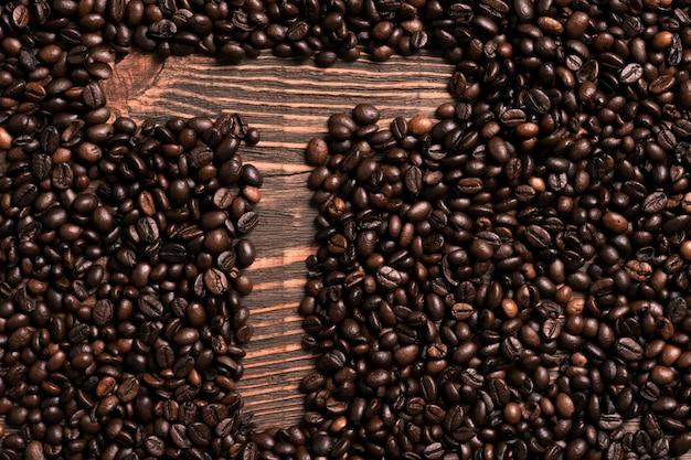 Буква t надпись с кофейным зерном на деревянном столе. вид сверху. скопируйте пространство. натюрморт. макет. плоская планировка