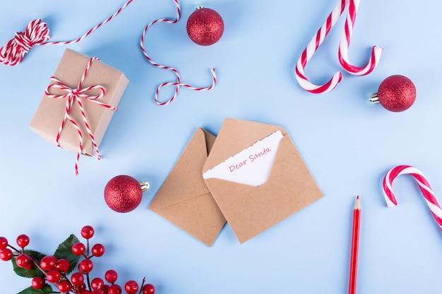 親愛なるサンタへの手紙。クリスマス休暇の背景に封筒を作成します。フラットレイ。
