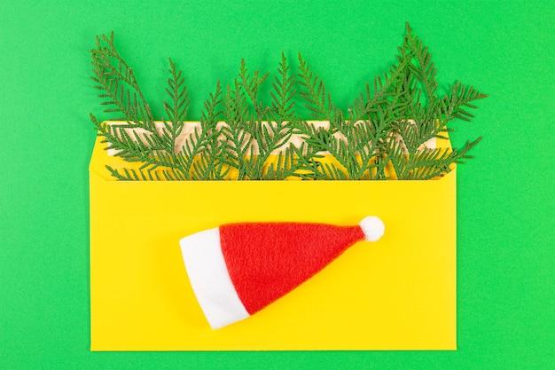 Письмо деду морозу. санта клаус красная шапка, конверт, еловая ветка. новый год и рождество концепции. плоская планировка, вид сверху с копией пространства.