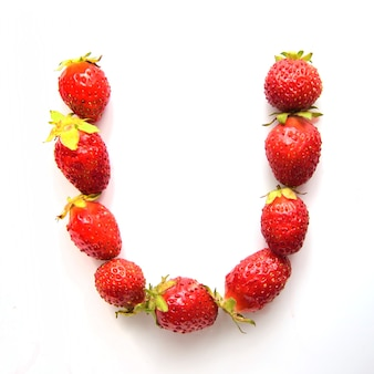 Letter u of the english alphabet of red fresh strawberries on white background