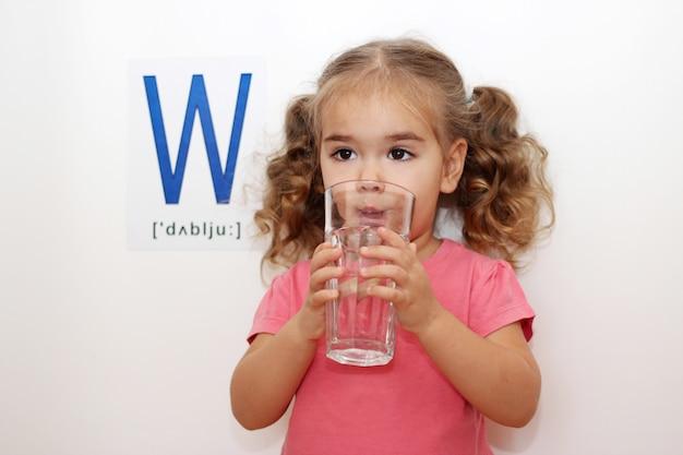 水としての文字「w」。かわいい小さな女の子飲料水
