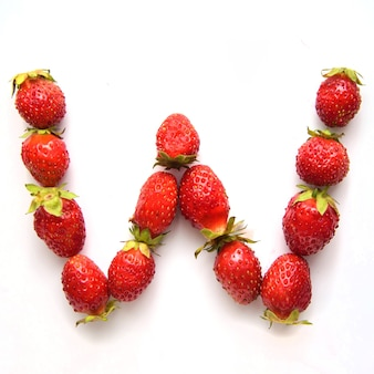 Буква w английского алфавита красной свежей клубники на белом фоне