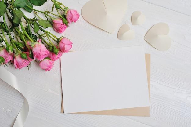 ピンクのバラと紙で作られた白い折り紙のハートの手紙、バレンタインデーのカード。