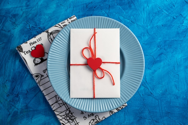 A letter with a heart on a blue plate