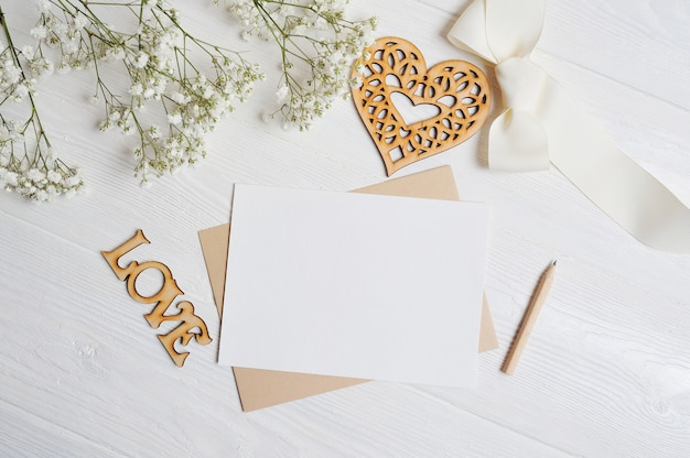 Letter with a love box in the shape of a heart lies on a wooden white table with gypsophila flowers