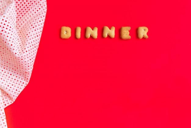 The letter word dinner. alphabet cookie cracker on red