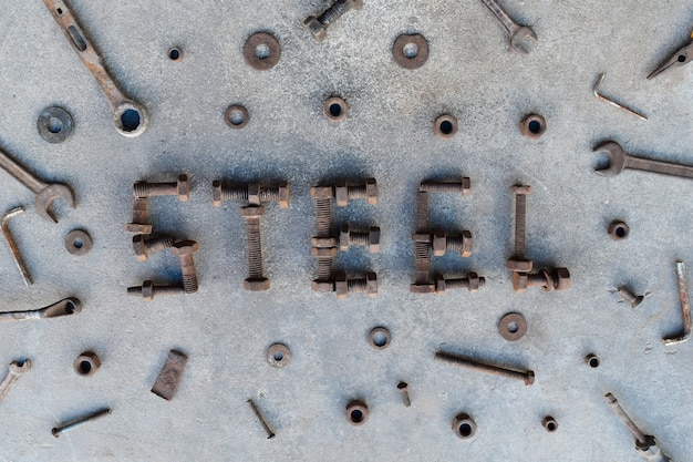 Letter word is steel by old and rusty nut on dirty ground