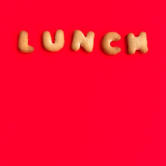 The letter word lunch. alphabet cookie cracker on red