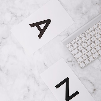 Letter a and z on white paper and keyboard on white marble textured background