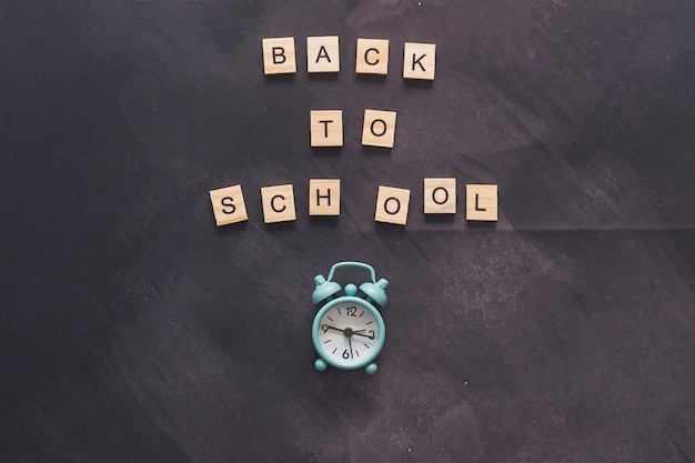 Lettering back to school on abstract textural chalk rub on graphite board or chalkboard background with alarm clock.dark wall background or learning concept.central location