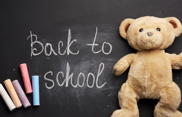 Lettering back to school in white chalk on a black school board and a piece of chalk, brown teddy bear