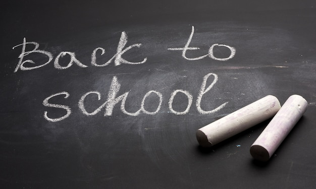 Lettering back to school in white chalk on a black school board and a piece of chalk, close up