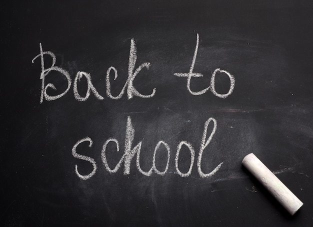 Lettering back to school in white chalk on a black school board and a piece of chalk