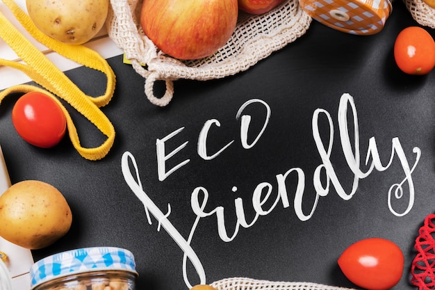 Lettering eco friendly, message on a black chalkboard and vegetables in a cotton eco sacs and glass jar with legume, use eco packeging in the kitchen