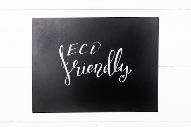Lettering eco friendly , message on a black chalkboard on a white wooden background
