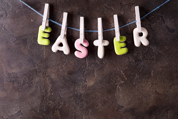 Lettering from cookies happy easter on stone background.