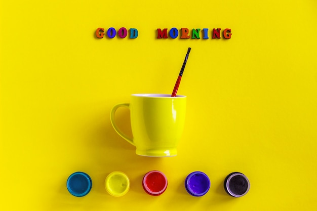 Lettering good morning, jars gouache and yellow cup with paintbrush. concept