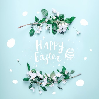 Lettering happy easter in a frame from the flowers of an apple tree on a pastel blue
