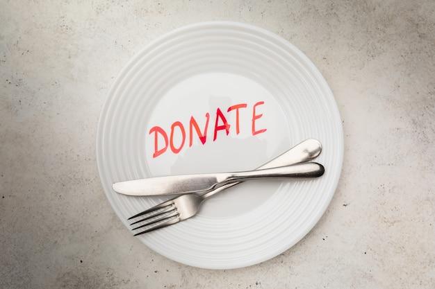 皿の上のレタリングとテーブルの上のカトラリー、上面図、食糧寄付の概念