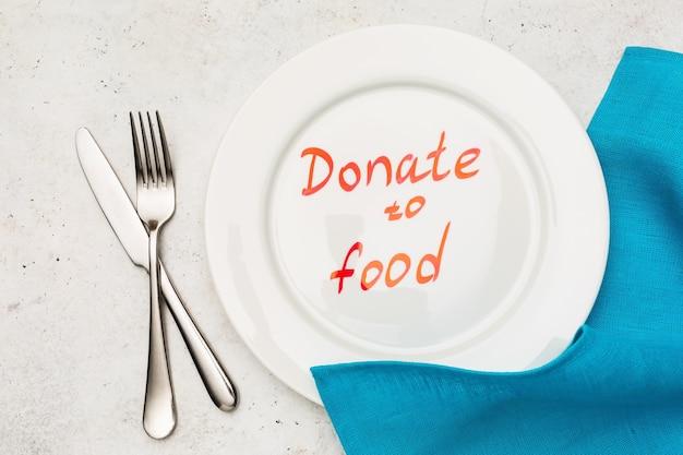 皿の上のレタリング、テーブルの上の青いテーブルクロスとカトラリー、食糧寄付の概念