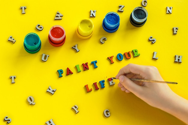 Lettering paint your life from colorful letters, hand with paintbrush