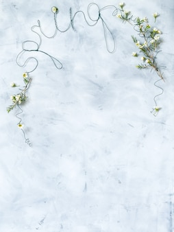 Lettering spring with white flowers on grey background