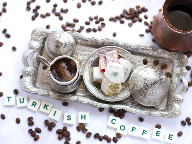 Lettering turkish coffee with traditional turkish sweets in a silver mug