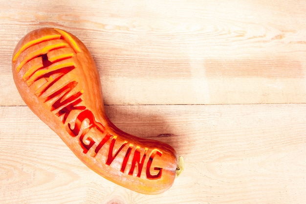 Lettering word 'thanksgiving' on a pumpkin