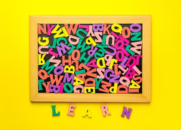 木製の文字に囲まれた黒板に文字abc。