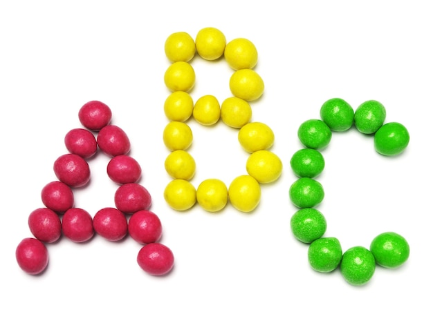 Letters a b and c from colored candy on white