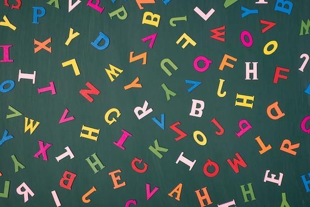 英語の言語概念を研究する手紙の背景。グリーンボード上で分離されたカラフルな文字の俯瞰写真の上の上