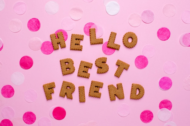 Letters cookies helllo best friend with confetti on pink