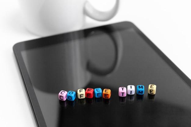 Письма куб блоков с кофе время концепции на экране планшета.