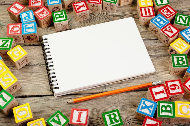 Letters cubes. wooden cubes with letters with blank notebook