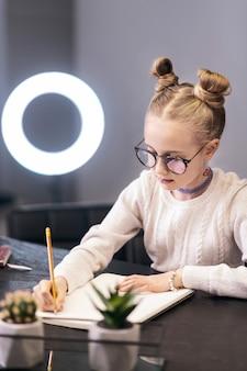 手紙。手紙を書く白いセーターを着ているかわいい青い目の長い髪の少女