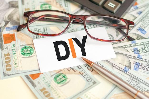 Буквы diy написаны на белой карточке, лежащей на купюрах, очках, ручке и калькуляторе