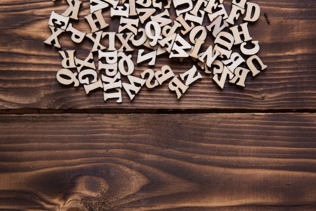 Letters of the english alphabet on a dark wooden background. the concept of education, word games, needlework. space for text