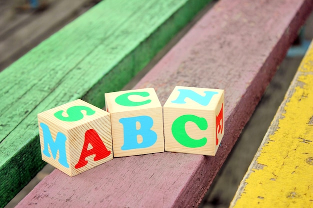 Letters of the english alphabet on wooden toy blocks which are on the old boards