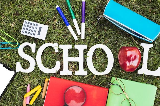 草の上の文房具の近くのリンゴと学校という言葉の手紙