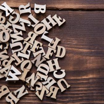 暗い木製の背景に英語のアルファベットの文字。教育、ワードゲーム、裁縫の概念。テキスト用のスペース