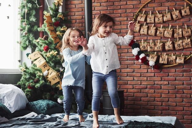 ツリーの文字はメリー クリスマスを意味します。楽しそうにベッドに飛び乗る元気な子供たち