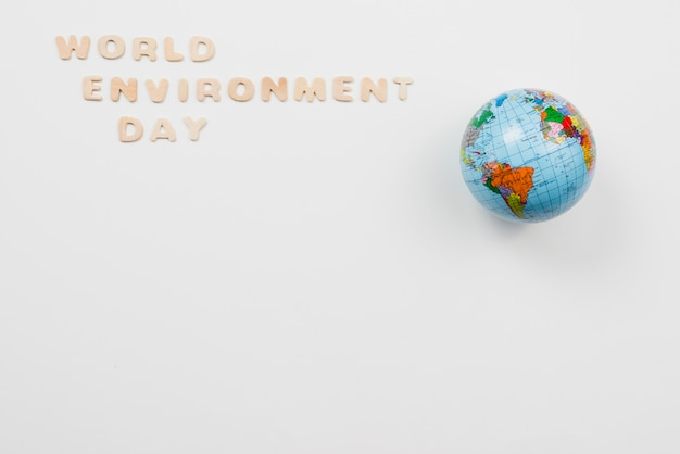 Letters in phrase world environment day beside globe