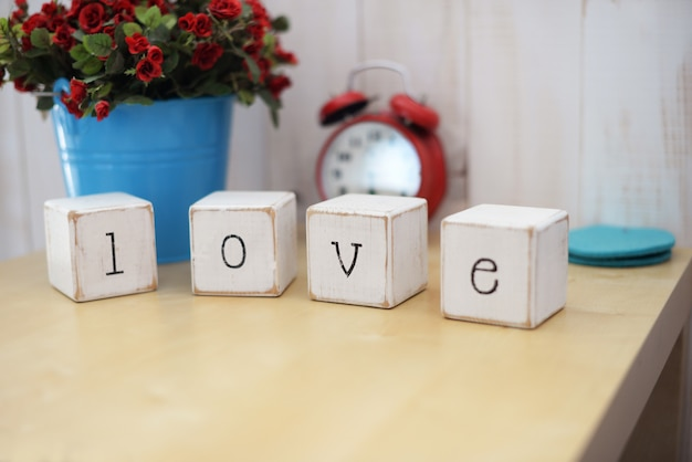 Letters wooden word cubes love on a table with a red alarm clock with a bouquet of flowers
