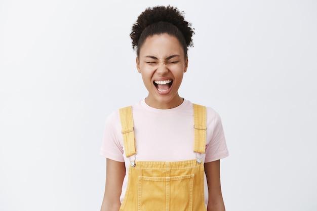 Выпустить эмоции - это хорошо. беззаботная красивая афроамериканка с гладкой и чистой кожей в желтом комбинезоне кричит с закрытыми глазами, снимает стресс, пытается успокоиться над серой стеной