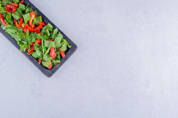 Insalata di lattuga e peperoni accatastati in un vassoio nero su fondo marmo. foto di alta qualità