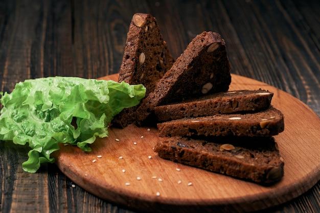 Листья салата и ржаной хлеб с кедровыми орехами на деревянной доске