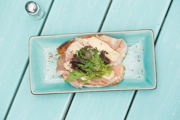 양상추, 모타 델라 및 치킨 샌드위치는 밝은 파란색 나무 테이블에 밝은 파란색 접시에 반으로 줄었습니다. 오버 헤드