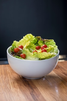 木製のテーブルに白いボウルにレタスのサラダとチェリートマト